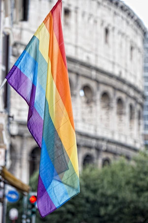 在罗马大剧场背景的彩虹旗子 免版税图库摄影