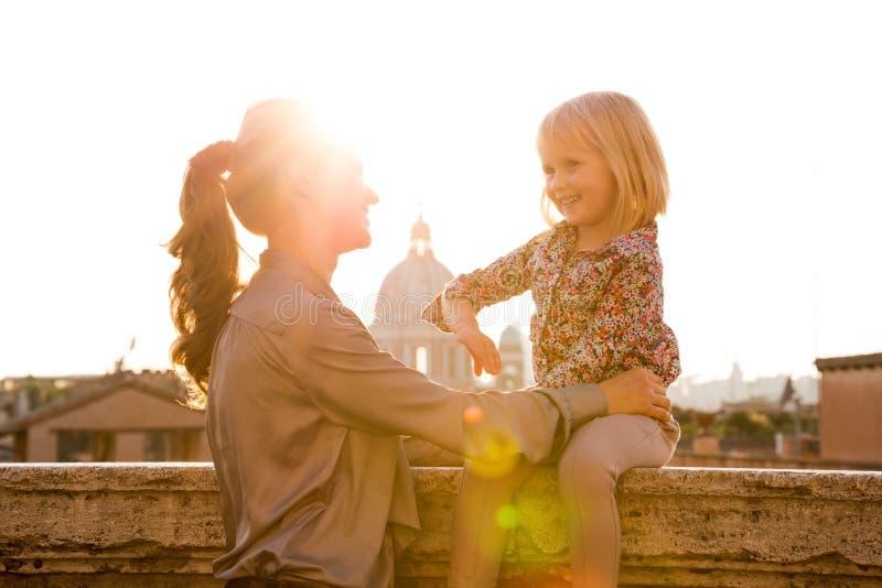 在罗马照顾拿着女儿坐壁架 免版税库存照片