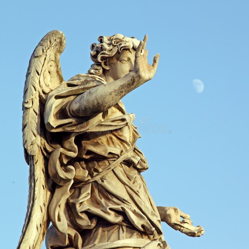 在罗马镀青铜一个天使的雕象,有在天空的苍白月亮的 免版税库存图片