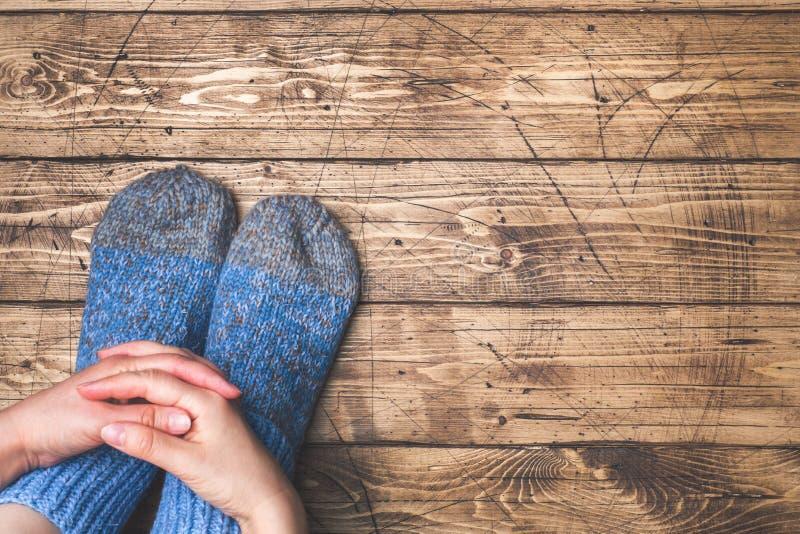 在羊毛制被编织的袜子的腿在木背景 复制空间 免版税库存照片