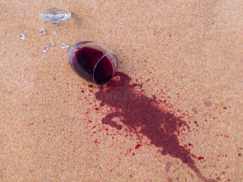 在羊毛地毯投下的红葡萄酒 免版税库存图片