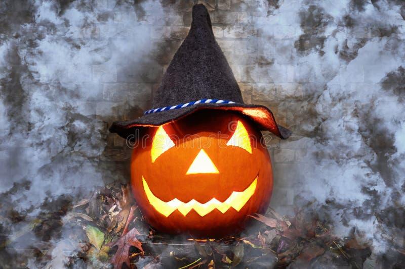 在羊毛帽子的发光的万圣节南瓜在叶子堆  一阵烟幕 免版税库存图片