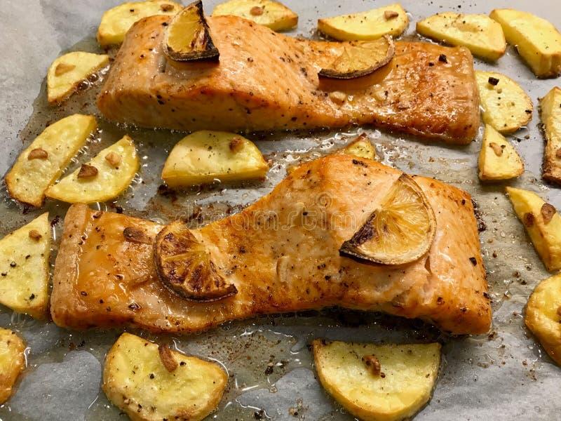 在羊皮纸的被烘烤的三文鱼内圆角用柠檬和土豆 免版税图库摄影