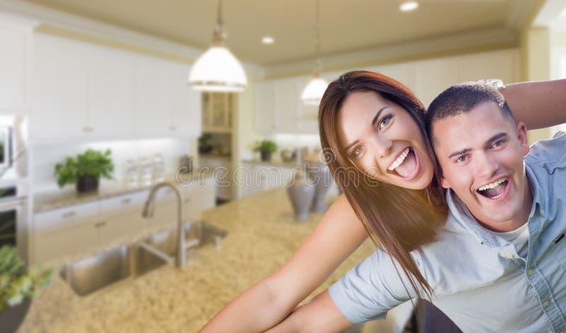 在美丽的习惯厨房里面的嬉戏的年轻军事夫妇 库存照片