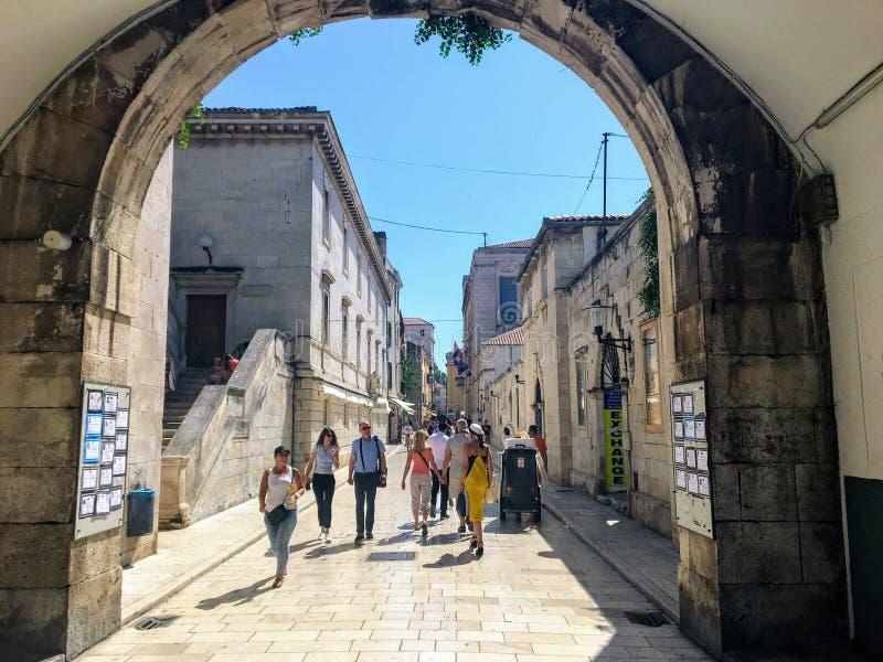 在美丽的夏日,一群群人从海门走进克罗地亚扎达尔老城区 库存图片