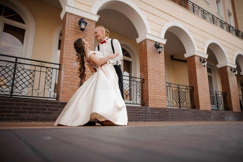 在美丽的大厦附近的愉快的年轻夫妇跳舞 库存图片