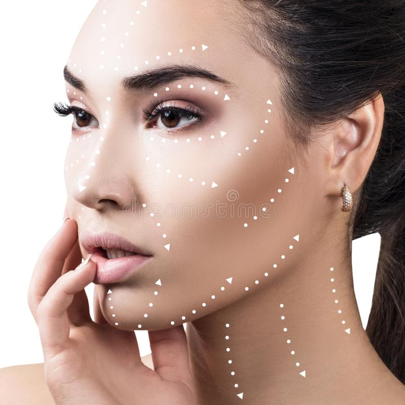 在美丽的女性面孔的按摩线显示方向 免版税库存照片