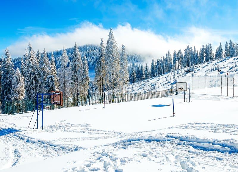 在美丽的山多雪的风景的篮球场 免版税库存图片