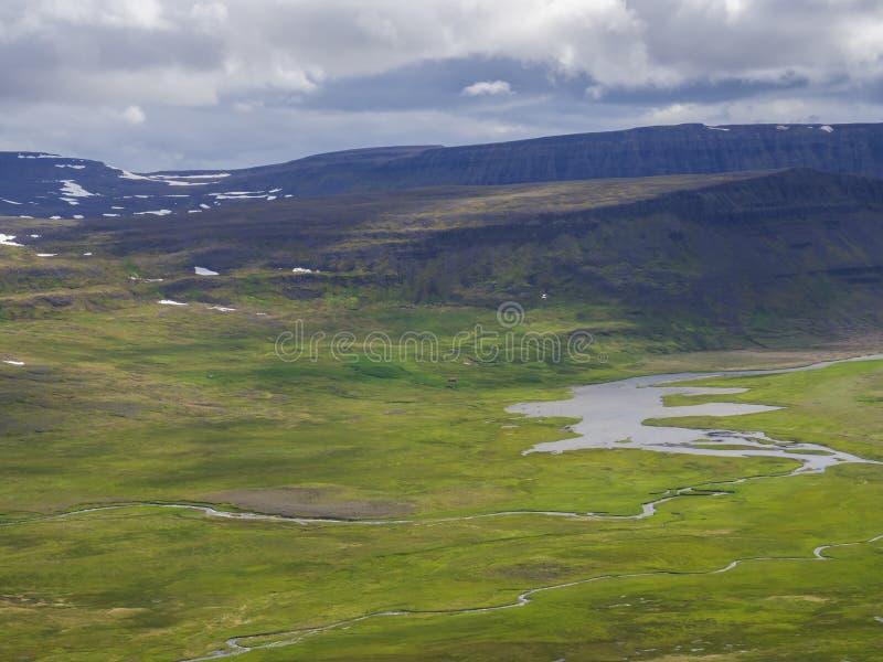 在美丽的峭壁的看法在西部海湾自然保护Hornstrandir的adalvik小海湾在冰岛,有河小河三角洲的 库存照片