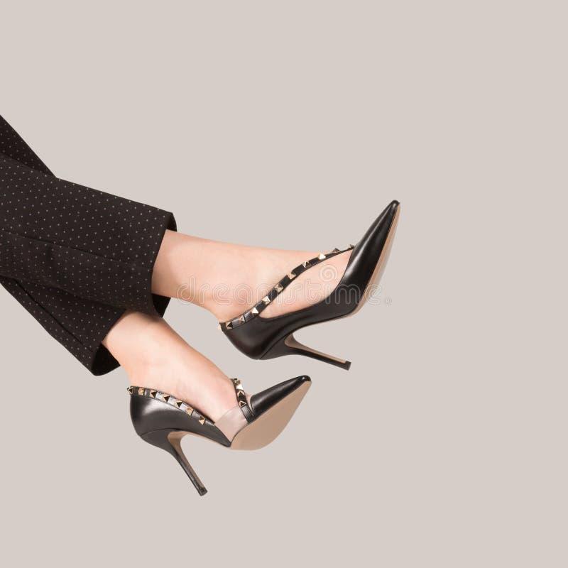 在美丽的昂贵的鞋子的女性腿有钉的 免版税库存图片