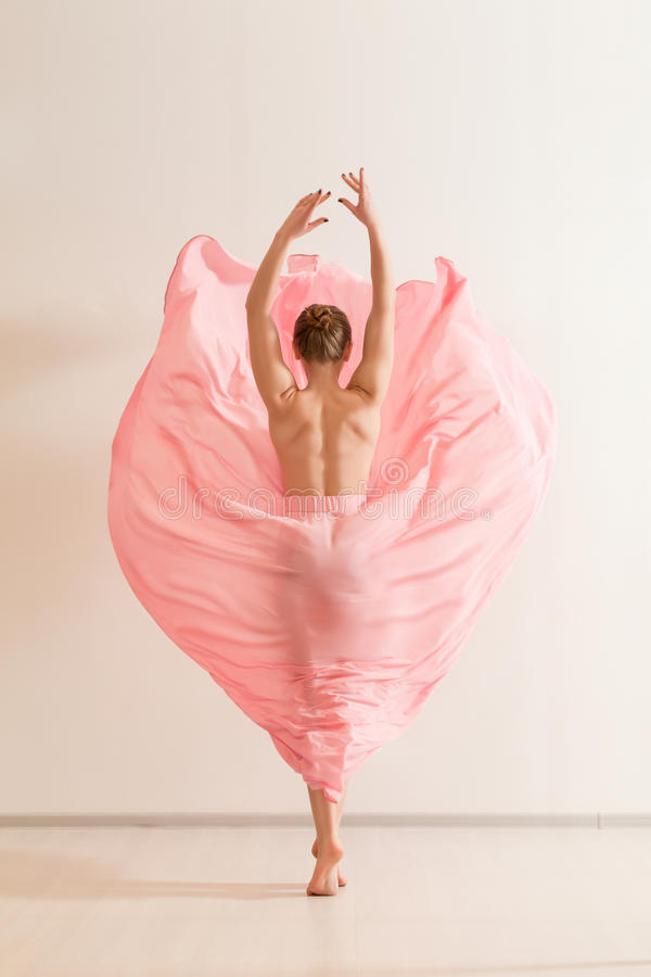 在美丽的桃红色礼服的少妇跳舞 库存照片