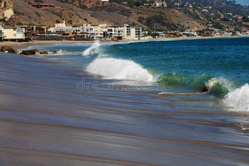 在美丽的沙滩、多云天空、太阳光芒、反射和起伏式波的心形的岩石在蓝色小时内在之后 免版税库存照片