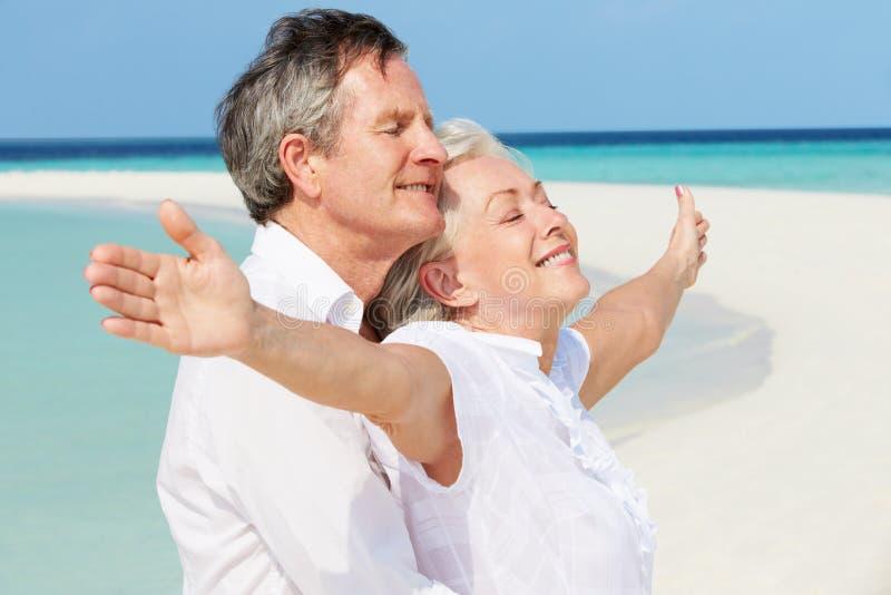 在美丽的海滩伸出的资深夫妇Withs胳膊 免版税库存照片