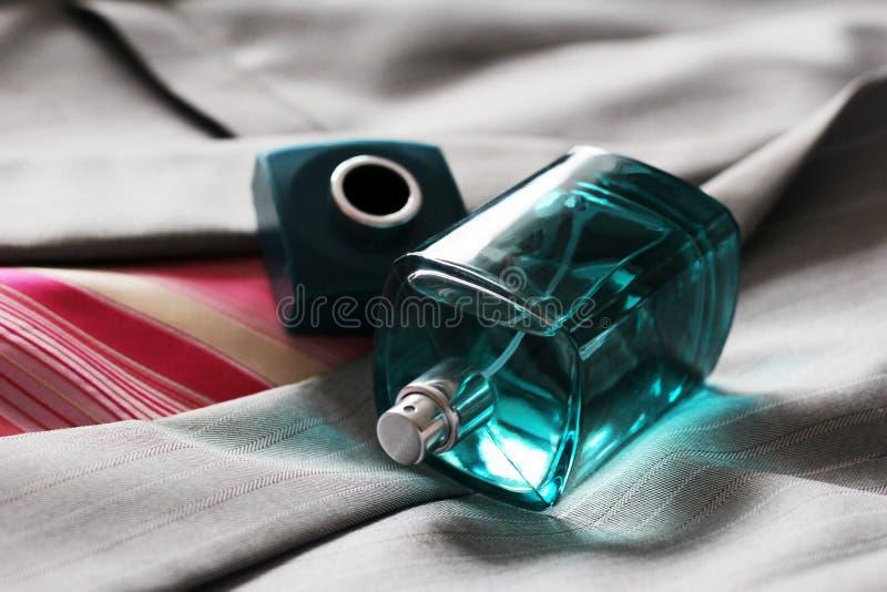 在美丽的瓶的人的香水在灰色夹克 库存照片