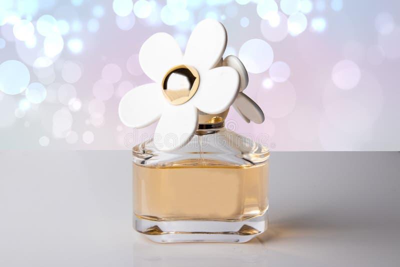 在美丽的瓶的豪华香水有作为穿孔机的白花的 图库摄影