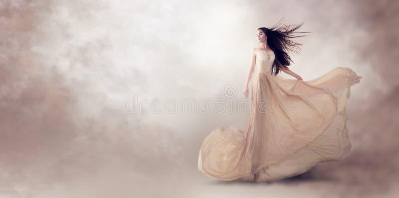 在美丽的米黄流动的薄绸的礼服的时装模特儿 免版税图库摄影