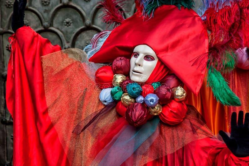 在美丽的红色服装的面具在狂欢节在威尼斯 图库摄影