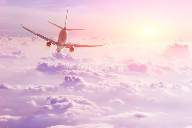 在美丽的蓬松云彩上的平面飞行在风景日落时间 旅行和假期概念 库存图片