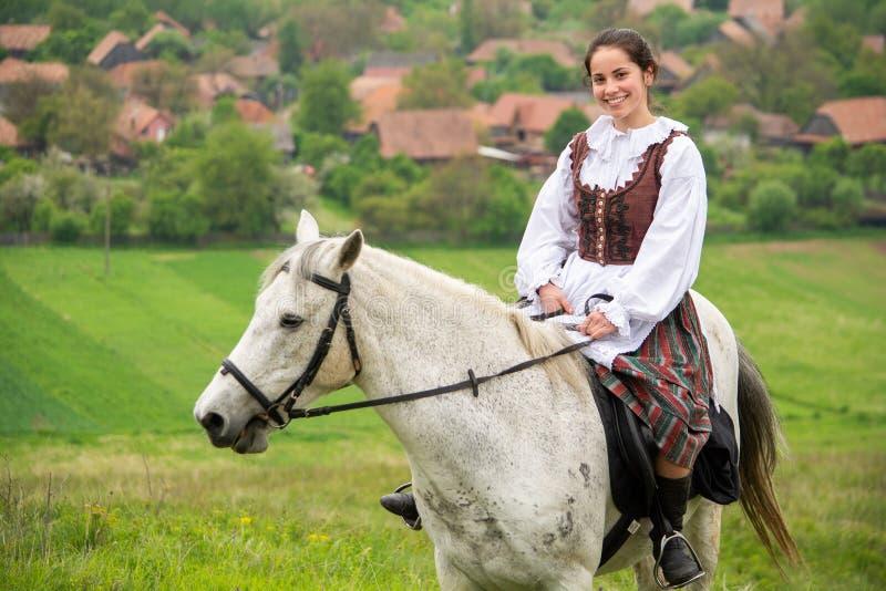 在美丽的马的少妇骑马,获得乐趣在夏时,罗马尼亚乡下 免版税图库摄影