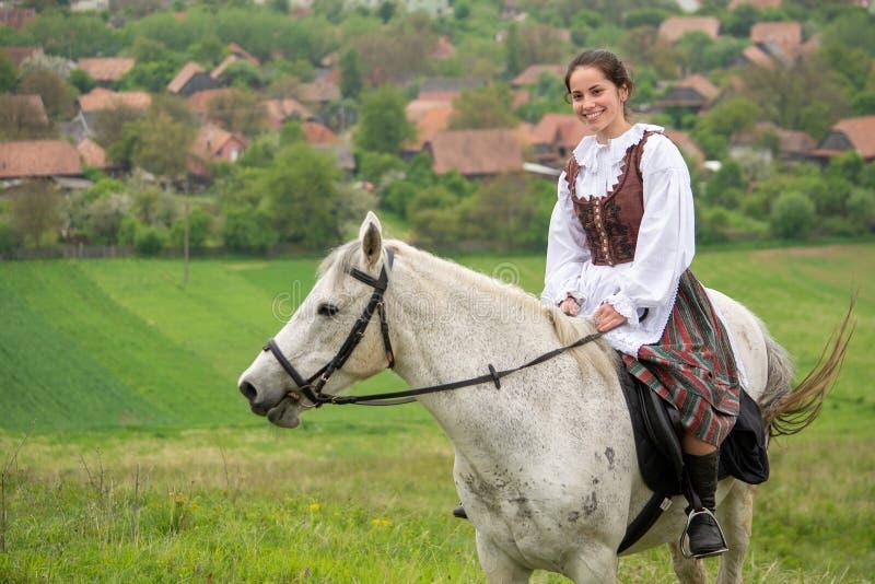 在美丽的马的少妇骑马,获得乐趣在夏时,罗马尼亚乡下 免版税库存照片