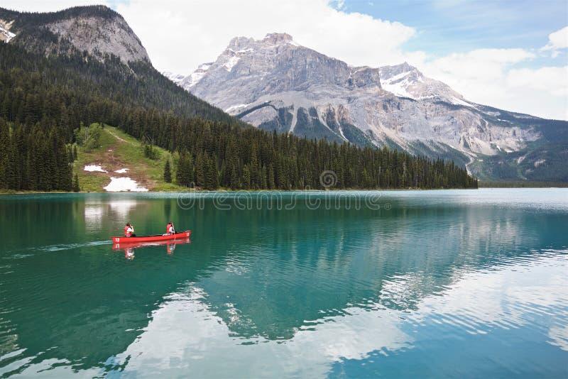 在美丽的鲜绿色湖的红色独木舟浮游物 库存图片