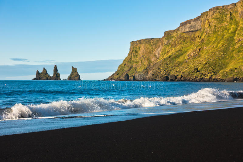 在美丽的黑火山的沙子的波浪在Vik靠岸在日出 库存照片