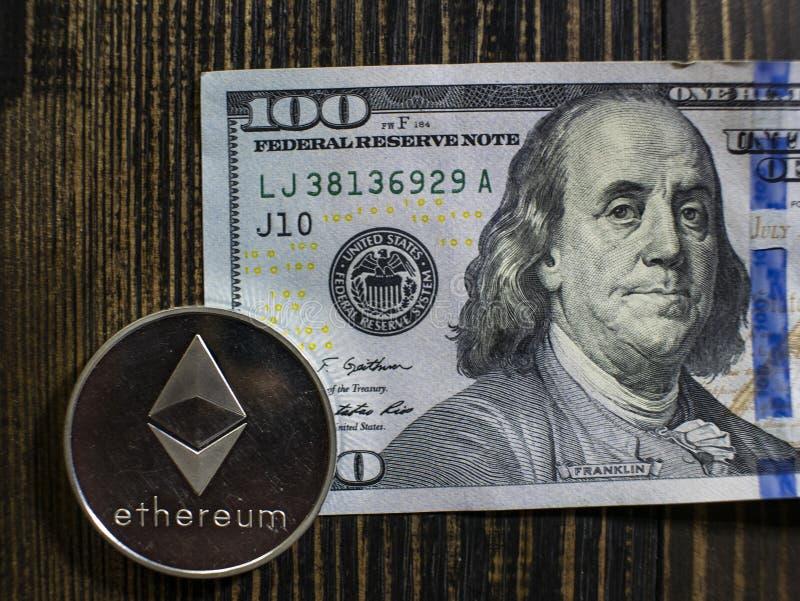 在美元的银色Ethereum 数字在木背景的货币特写镜头 bitcoin真正的硬币在钞票的一百 图库摄影