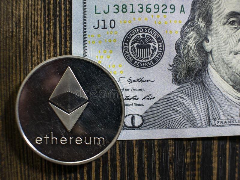 在美元的银色Ethereum 数字在木背景的货币特写镜头 bitcoin真正的硬币在钞票的一百 免版税库存照片