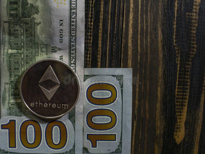 在美元的银色Ethereum 数字在木背景的货币特写镜头 bitcoin真正的硬币在钞票的一百 库存照片