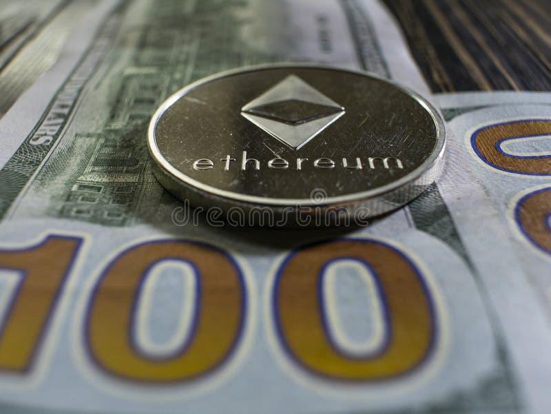 在美元的银色Ethereum 数字在木背景的货币特写镜头 bitcoin真正的硬币在钞票的一百 免版税图库摄影
