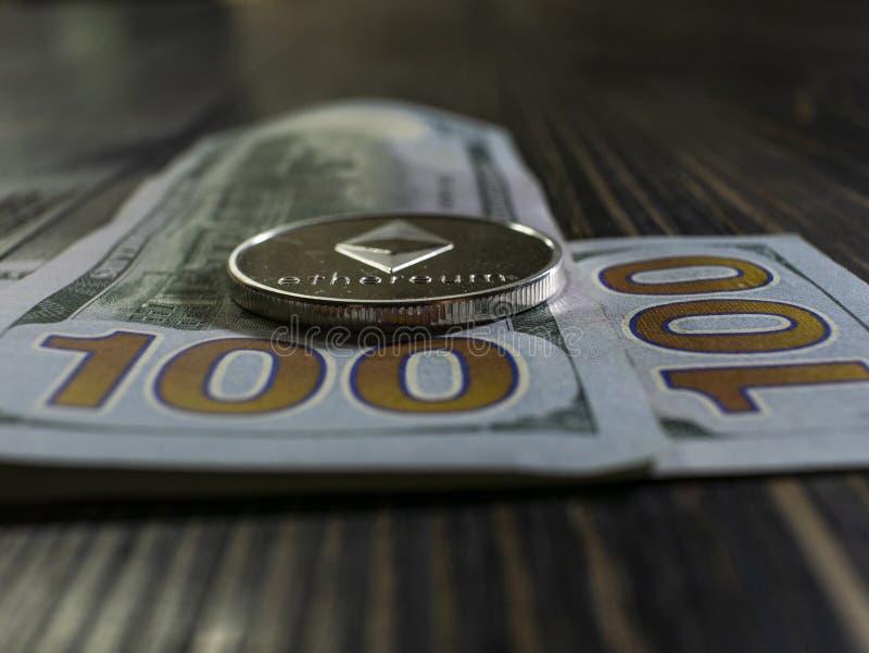 在美元的银色Ethereum 数字在木背景的货币特写镜头 bitcoin真正的硬币在钞票的一百 库存图片