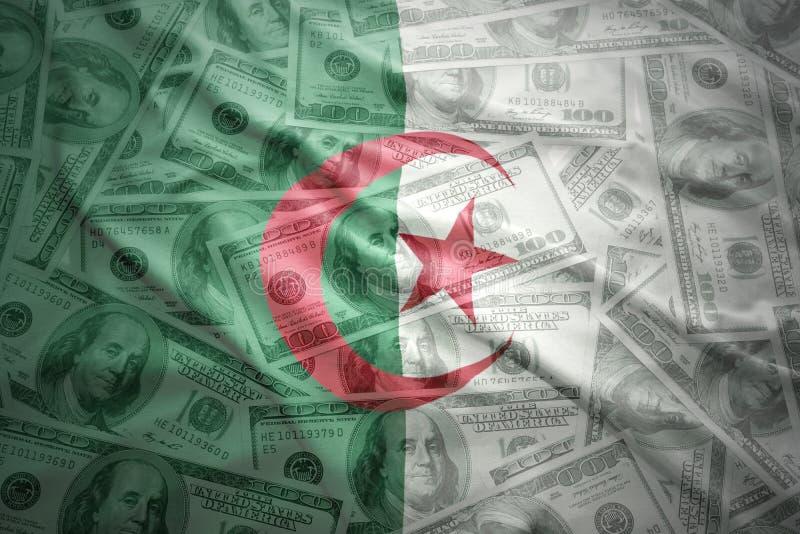 在美元金钱背景的五颜六色的挥动的阿尔及利亚的旗子 免版税库存图片