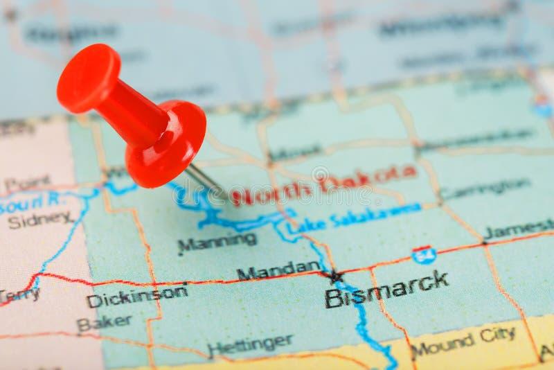 在美国、北达科他和首都俾斯麦地图的红色职员针  与红色大头钉的特写镜头地图北达科他 ?? 免版税库存照片