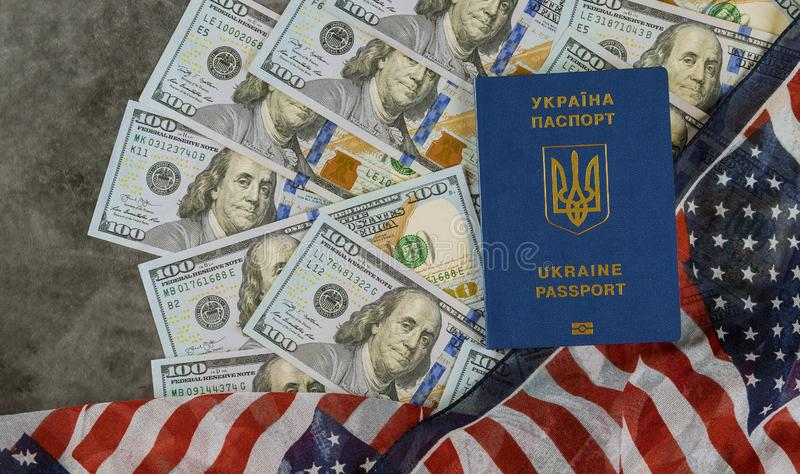 在美国旗子的乌克兰生物统计的护照与一百美元票据  库存照片