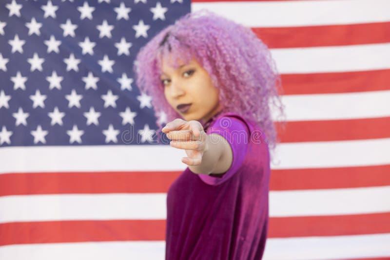 在美国旗子隔绝的年轻黑人妇女指向y 库存照片