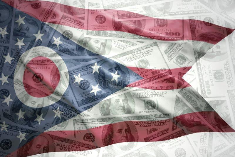 在美国美元金钱背景的五颜六色的挥动的俄亥俄状态旗子 免版税库存图片