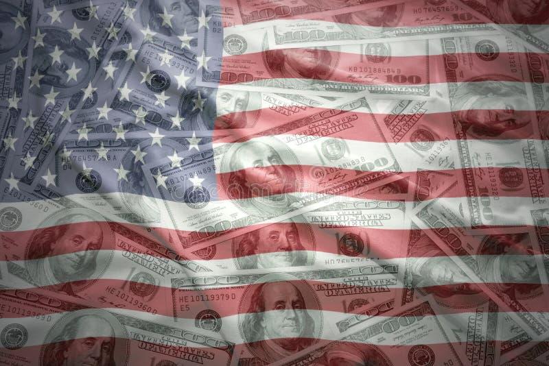 在美国美元金钱背景的五颜六色的挥动的美国旗子 免版税库存图片