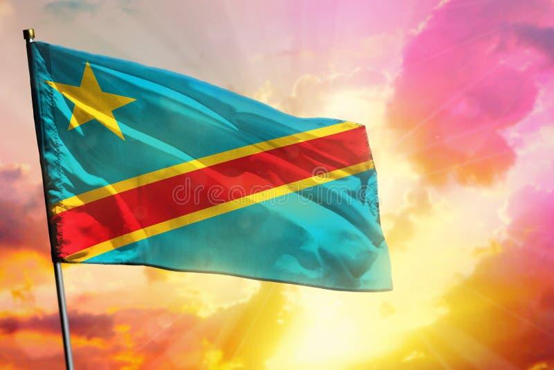 在美好的五颜六色的日落或日出背景的振翼的刚果民主共和国旗子 球尺寸三 免版税库存照片