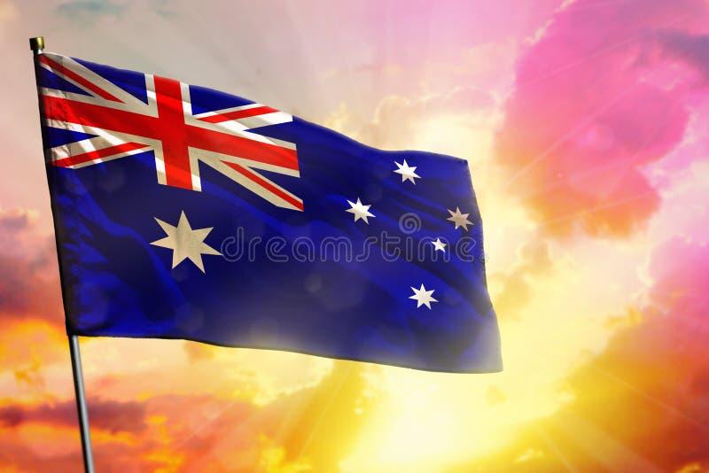 在美好的五颜六色的日落或日出背景的振翼的澳大利亚旗子 球尺寸三 库存照片