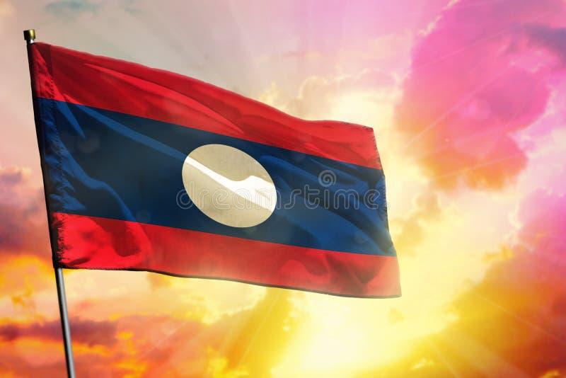 在美好的五颜六色的日落或日出背景的振翼的老挝人人民主共和国旗子 : 库存例证