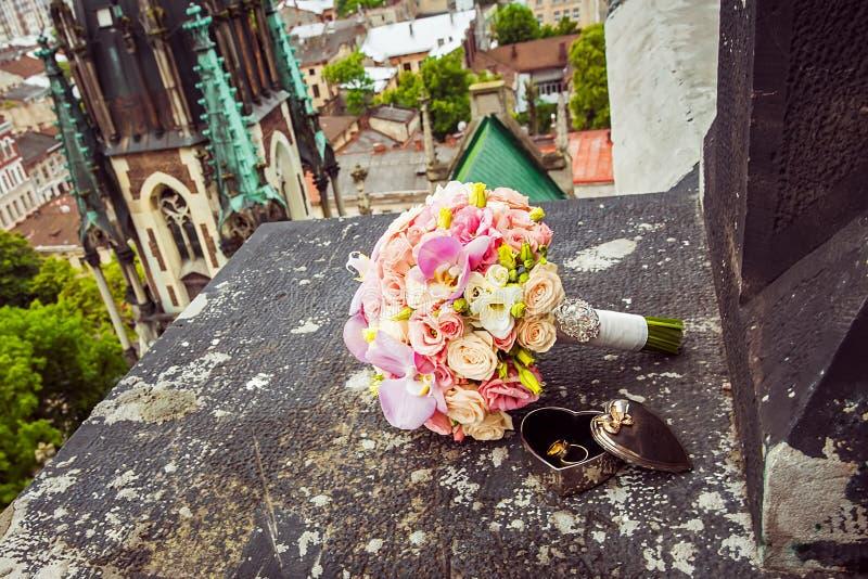 在美好的形状的两个金子婚戒以心脏和桃红色花的形式花束在窗口基石边缘的 免版税库存图片