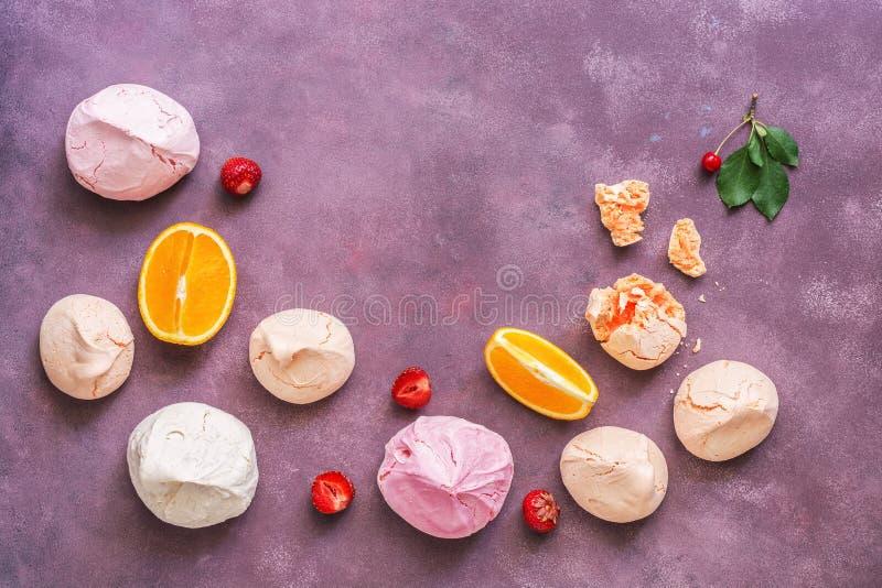 在美好的抽象紫色背景的多彩多姿的莓果蛋白甜饼 顶视图,拷贝空间 图库摄影