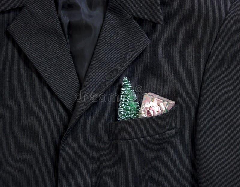 在美好的条纹衣领口袋袖子的人` s黑暗的与弓的夹克在口袋圣诞树和礼物变粉红色包裹 库存照片