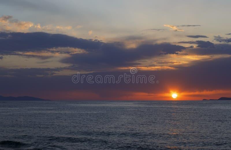 在美好的橙色蓝色云彩和水平线之间的红色太阳在日落的晚上, 免版税库存照片