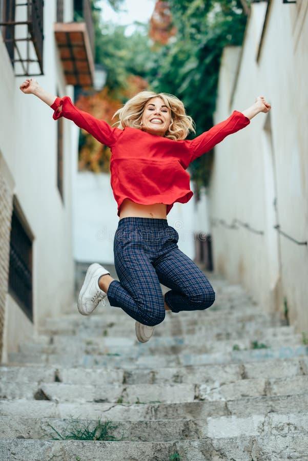 在美好的步的愉快的年轻白肤金发的妇女身分在街道 免版税库存照片