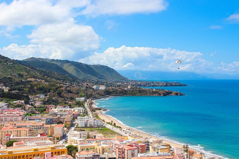在美好的海景上的滑翔伞飞行由城市切法卢在西西里岛,意大利 滑翔伞是普遍的冒险体育 免版税库存照片