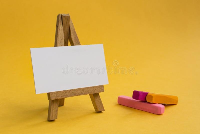 在美好的色的背景的木画架 库存照片