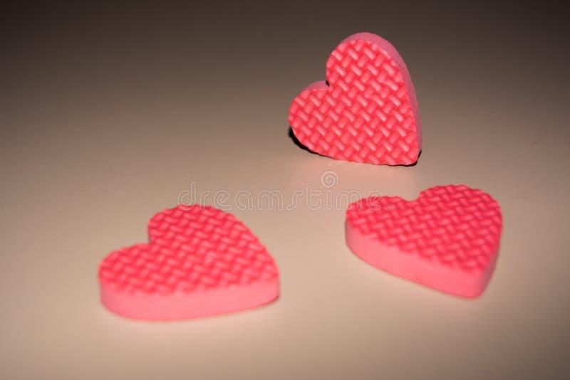 在美好的轻的背景的三美好的桃红色心脏 日s华伦泰 免版税库存图片