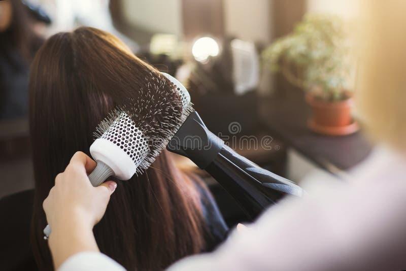 在美容院的美发师干燥妇女` s头发 免版税库存照片