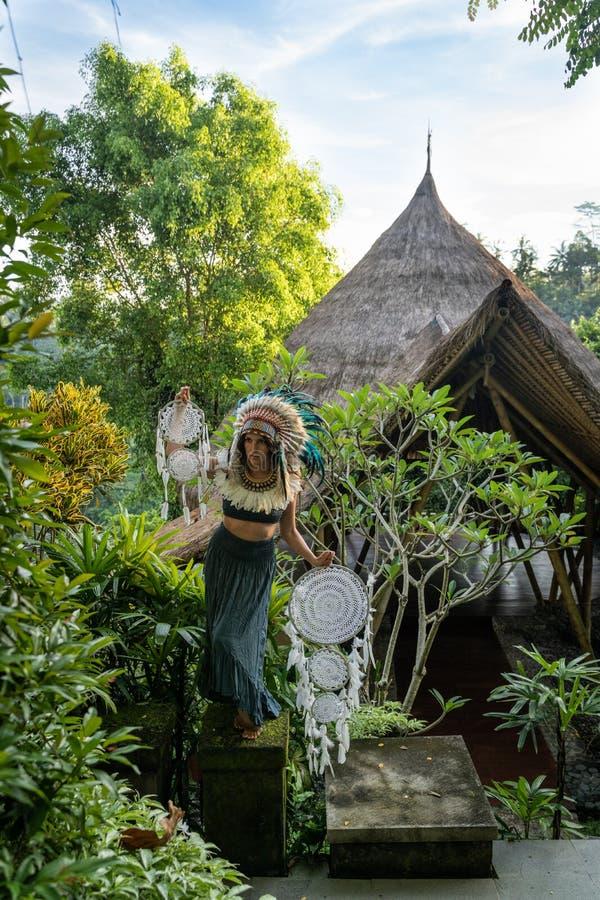 在美洲印第安人穿戴的模型摆在与在藤茎屋顶大厦和绿叶前面的白色梦想俘获器 图库摄影